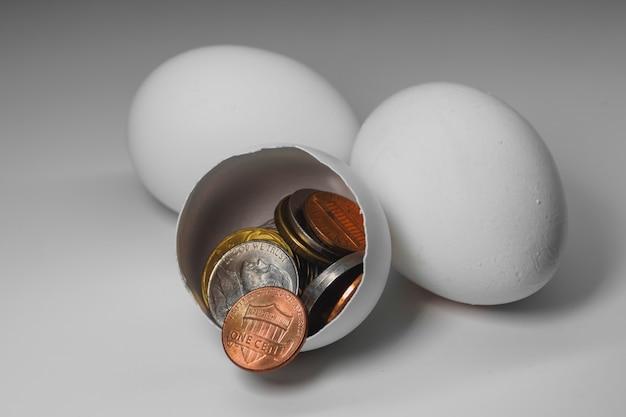2つの丸ごと1つの壊れた白い鶏の卵とそれらから落ちたアメリカのセント