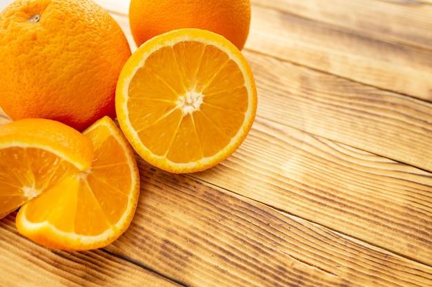 Два целых и нарезанных апельсина на деревянном фоне (крупный план)