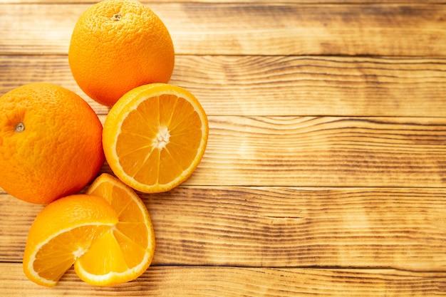 Два целых и нарезанных апельсина на деревянном фоне, вид сверху