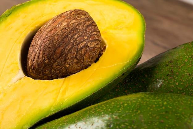 Два целых авокадо и разрезанный пополам авокадо на белой поверхности.