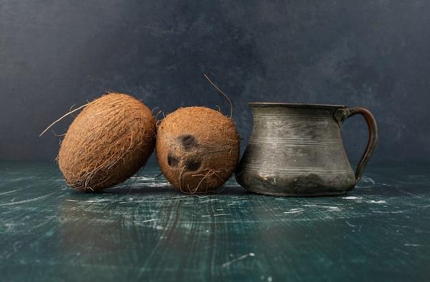 Due noci di cocco intere e vaso classico sulla tavola di marmo.