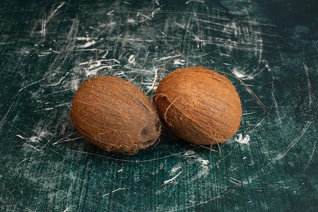 Due noci di cocco intere sulla tavola di marmo.