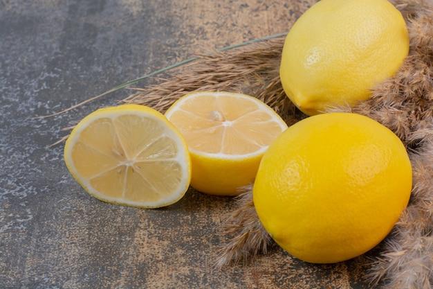 Due limoni freschi interi con fetta su spazio in marmo