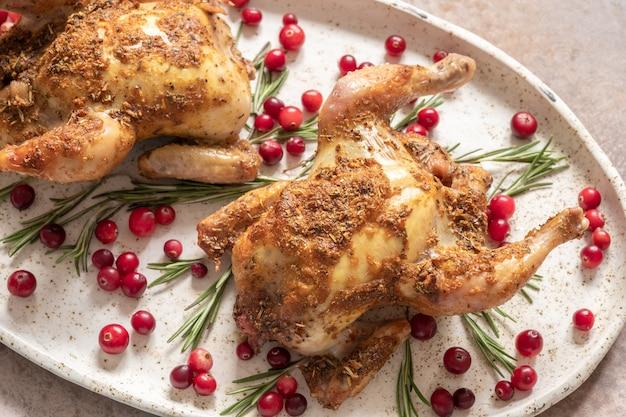 Два целых жареных цыпленка с клюквой и дольками апельсина.