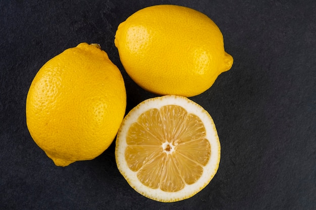 Два целых сицилийских лимона и одна половина на темном сланце.