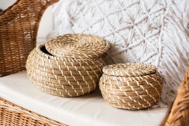 籐の椅子に、つるで作られた2つの籐のバスケット。枕マクラメ。エコ、天然素材、環境にやさしい。自由奔放に生きるスタイル。