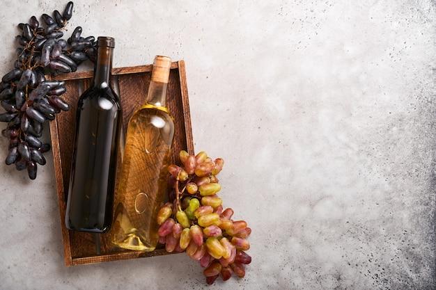 복사 공간이 있는 오래된 회색 콘크리트 테이블 배경에 포도와 와인잔이 든 두 개의 와인 병. 포도 나무 가지와 레드 와인입니다. 소박한 배경에 와인 구성입니다. 조롱.
