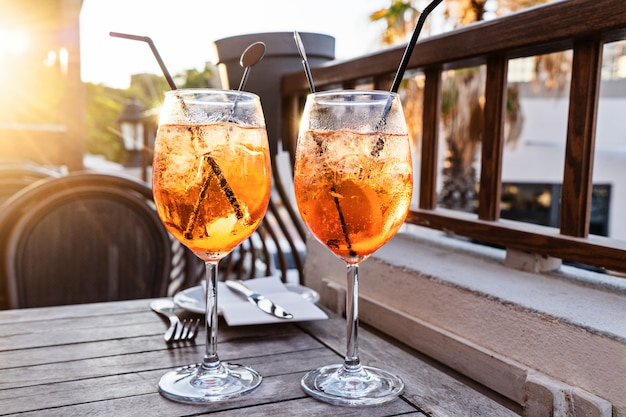 Two wine glass of cold cocktail aperol spritz on table