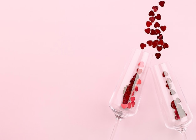 Два бокала и конфетти, разбросанные в виде сердечек на розовой стене