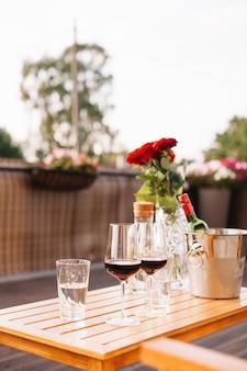 屋外のレストランで2本のワイングラスとバラ