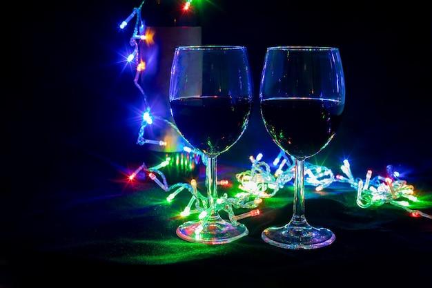 장난감 크리스마스 트리가 있는 빛나는 화환에 두 개의 와인 잔.
