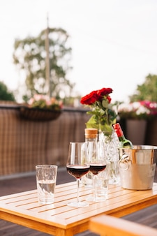 Two wine glasses and roses on an outdoor restaurant