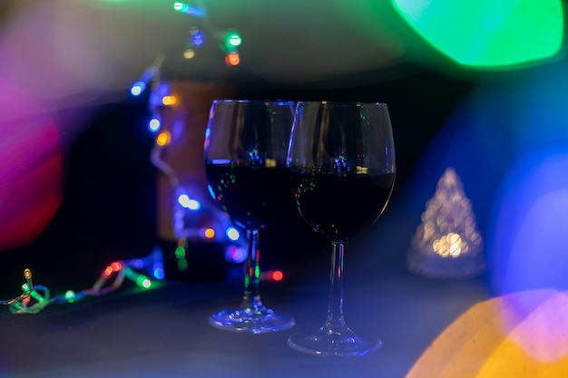 Two wine glasses in a shining garland bokeh on a black background