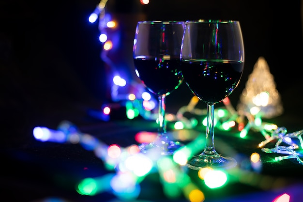 Two wine glasses in a shining garland with a toy christmas tree.