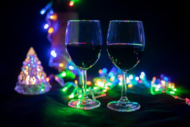 Two wine glasses in a shining garland with a toy christmas tree