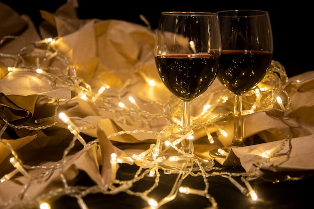 Two wine glasses stand in a shining yellow garland on craft paper cozy romantic celebration
