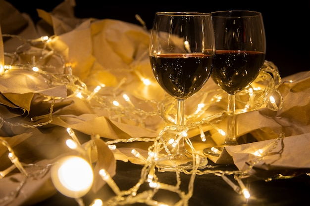 Two wine glasses stand in a shining yellow garland on craft paper. cozy romantic celebration...