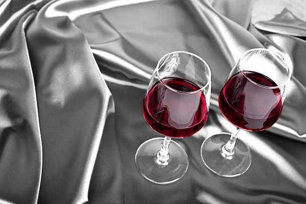 Two wine glasses with red wine on the gray silk