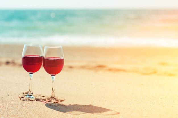 海岸のビーチの砂の上に赤ワインと2つのワイングラス。ロマンチックなカップル。