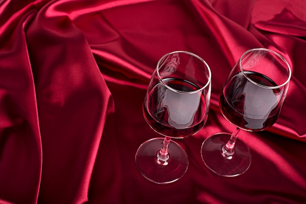 Two wine glasses with red wine on the red silk