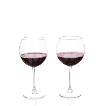 Two wine glasses with red wine on white wall