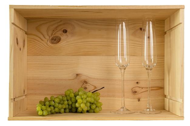コピースペースのあるワインボトルからの木製の箱に入ったシャンパンと白ブドウ用の2つのワイングラス