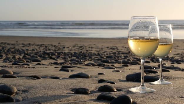 로맨틱 데이트 바다 물 일몰 파도를위한 화이트 와인과 함께 오션 비치 안경에 두 개의 와인 잔