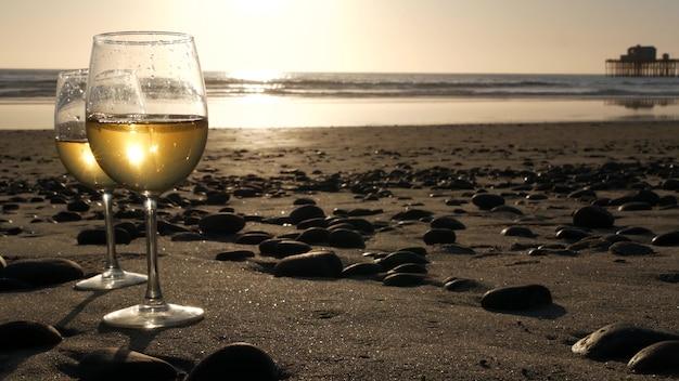 바다 해변에 두 개의 와인잔입니다. 로맨틱한 데이트를 위한 화이트 와인이 든 안경, 바닷물. 일몰 파도입니다.