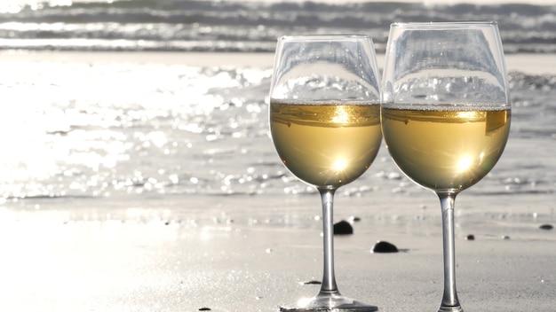 모래 바다 해변에 두 개의 와인잔입니다. 안경과 자갈 몇 개, 바다 근처에서 낭만적인 데이트를 위한 화이트 와인. 조수 파도 근처의 아늑한 해변 일몰입니다. 원활한 루프 시네마그래프. 미국 캘리포니아.