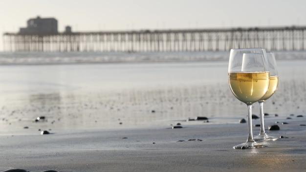 모래 바다 해변에 두 개의 와인 잔입니다. 몇 잔, 바닷물 근처에서 낭만적 인 데이트를위한 화이트 와인. 캘리포니아, 미국.