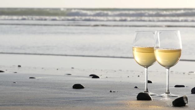 모래 바다 해변에 두 개의 와인잔입니다. 바다 근처에서 낭만적인 데이트를 위한 안경, 화이트 와인