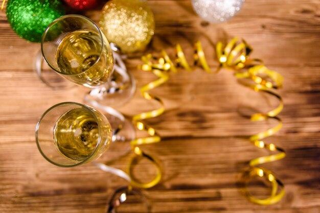 素朴な木製のテーブルにシャンパンとさまざまなクリスマスの装飾が施された2つのワイングラス。上面図
