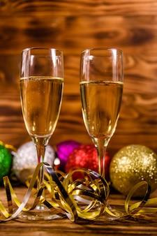素朴な木製のテーブルにシャンパンとさまざまなクリスマスの装飾が施された2つのワイングラス