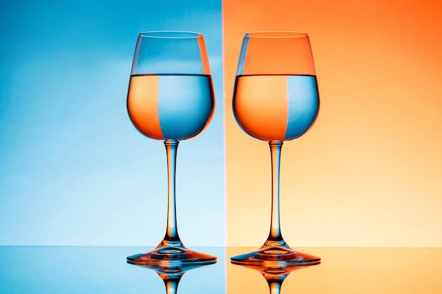 Two wineglasses with water over blue and orange background.