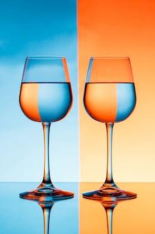 Due bicchieri di vino con acqua sulla parete blu e arancione