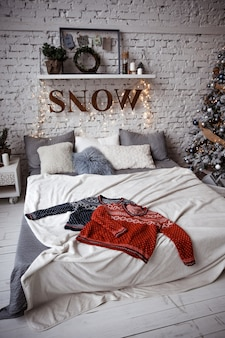 Two winter sweaters laid on a bed in a loft on the background of a brick wall
