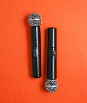 Два беспроводных микрофона на оранжевом фоне. плоская планировка. вид сверху