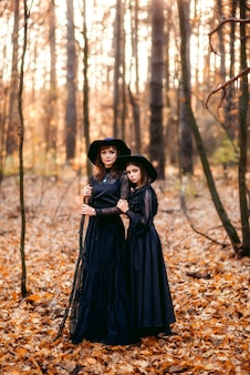 Two witches in the autumn forest. mother and daughter in black dresses.
