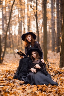 Two witches in the autumn forest. mother and daughter in black dresses..