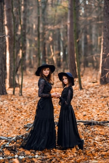 Two witches in the autumn forest. mother and daughter brew a potion.
