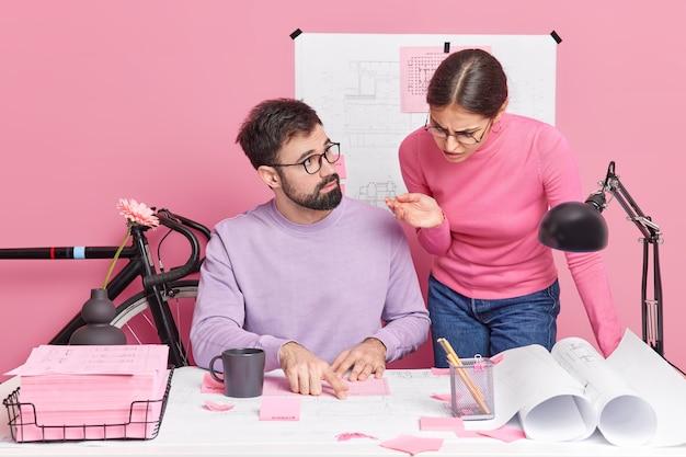 2人の女性と男性の学生が協力してレポートのプロジェクト作業の計画を立て、互いに相談し、チェックスケッチの周りの紙やスケッチでデスクトップでポーズをとるアイデアを共有します。