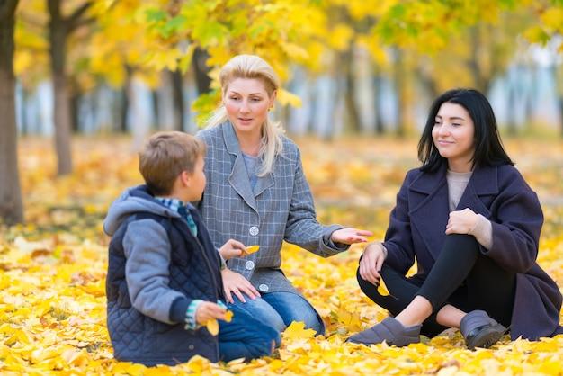 두 여자와 공원에서 십 대 소년 밝은 노란색 잎으로 덮여 바닥에 앉아 함께 채팅