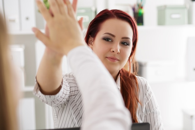 Two woman celebrating something giving high five at the office
