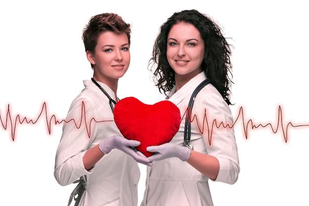 白い背景に赤いハートを保持している2人の女医師
