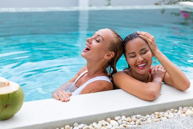 ヴィラのプールで化粧をしているアジア人と白人の2人の女性の友人