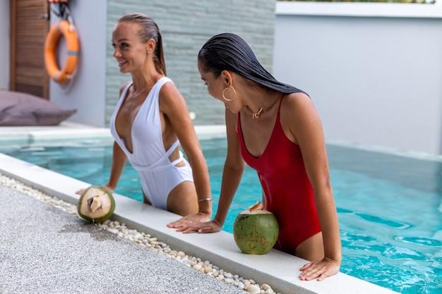 Две подруги азиатские и кавказские с косметикой в бассейне на вилле