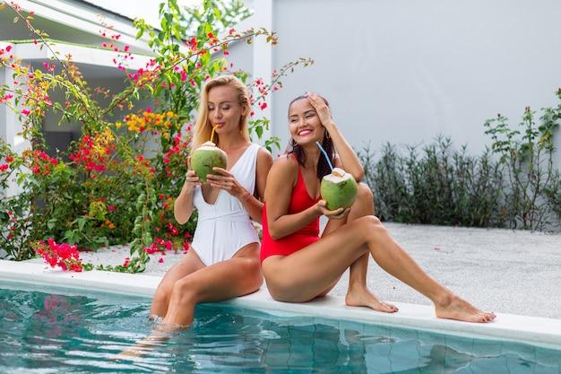 Две подруги азиатские и кавказские с косметикой на краю бассейна на вилле подружки с кокосами в отпуске у синего бассейна и цветочного дерева