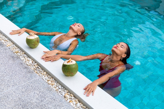 Two woman friends asian and caucasian with makeup in swimming pool at villa