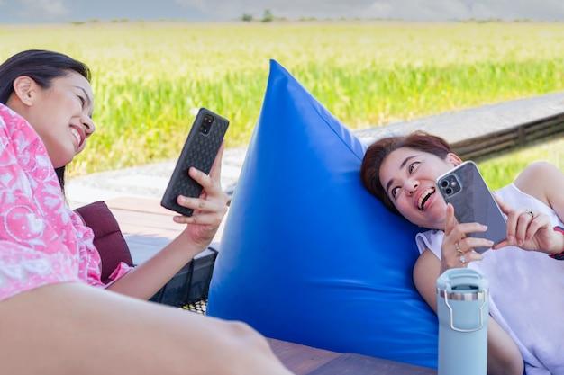 쿠션에 누워 스마트 폰을 사용하는 두 여자 친구