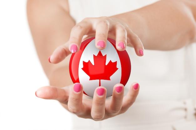 白い背景の上のカナダの旗地球グローブ球を保護する2つの女性の手。